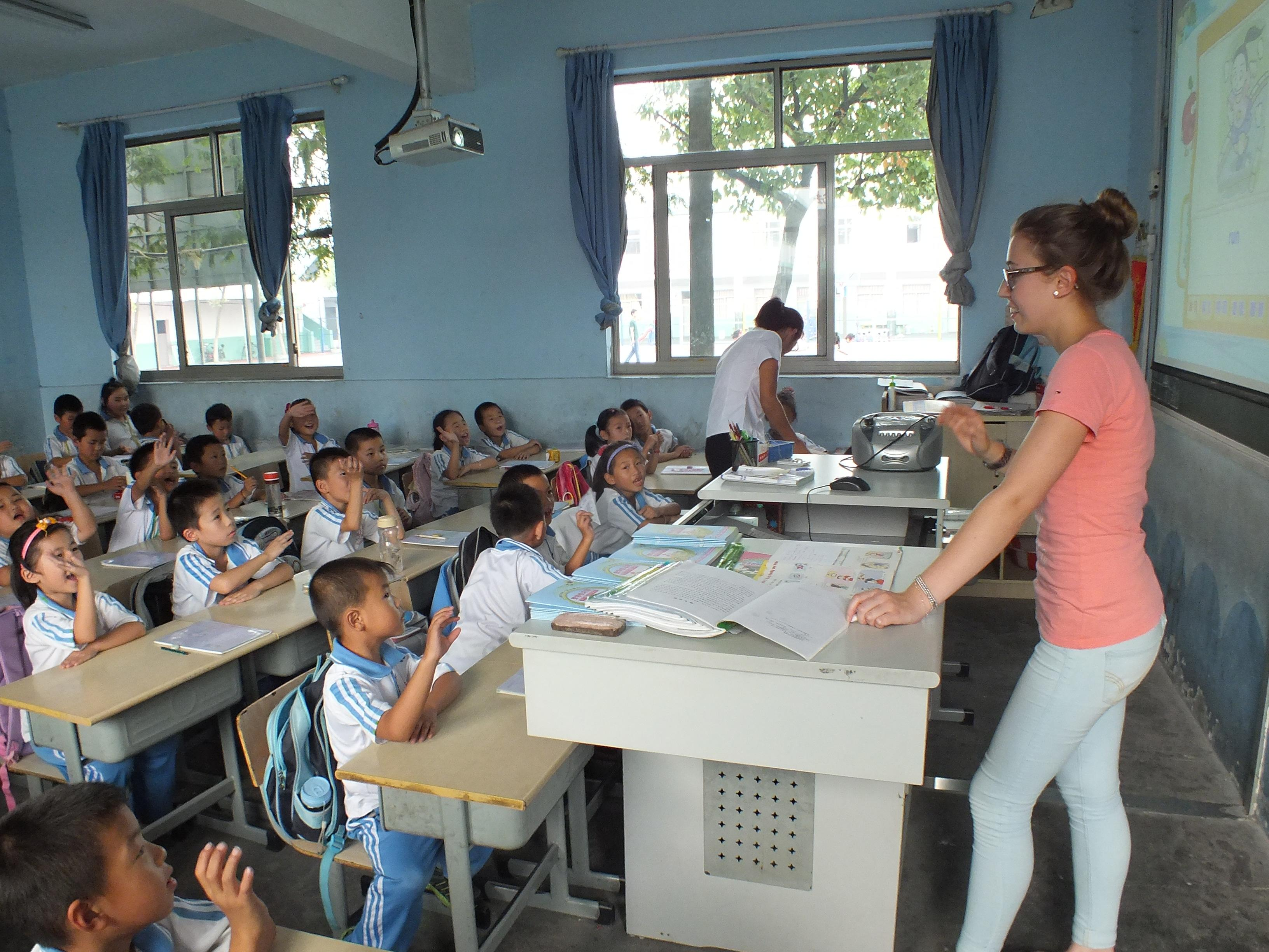 Young students put up their hands to answer the Projects Abroad volunteer teaching English in China